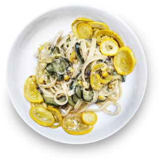 Bowl of pasta with zucchini, squash and corn.