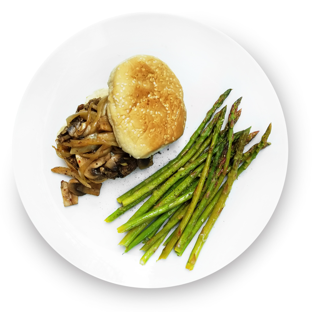 Lentil and olive veggie burger on a bun with asparagus on the side.