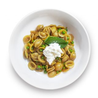 Pasta with green peas, mint and ricotta in a bowl.