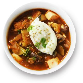 Kimchi jjigae in a bowl with a poached egg.